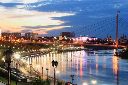 Foto de Paseo de noche de la ciudad de Tyumen. Quay(embankment) de la noche de la ciudad de Tyumen es iluminado por muchas lámparas, la luz que se refleja en la superficie del agua del río Tour. Paisaje muy hermoso - Imagen libre de derechos
