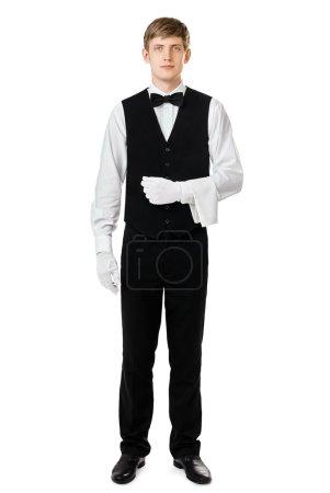 Photo pour Portrait complet de beau garçon élégant debout avec serviette sur le bras isolé sur fond blanc - image libre de droit