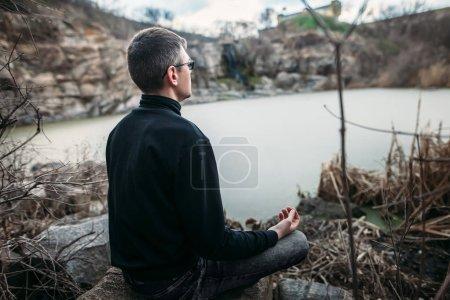 Homme méditant sur une falaise rocheuse avec vue sur le fleuve
