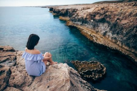 young woman sitting on Greco cape
