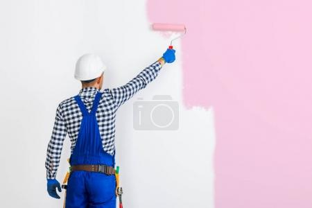 painter man painting wall in pink