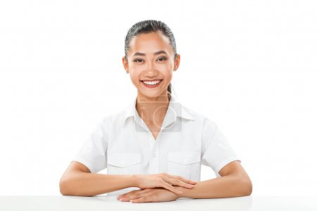 Asian girl in white shirt sitting at table