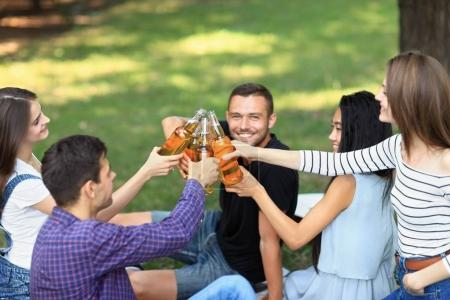 Photo for Five young happy friends clinking bottles of beer, laughing and having fun in nature. Cheerful girls and boys in casual summer clothes sitting on grass in park - Royalty Free Image