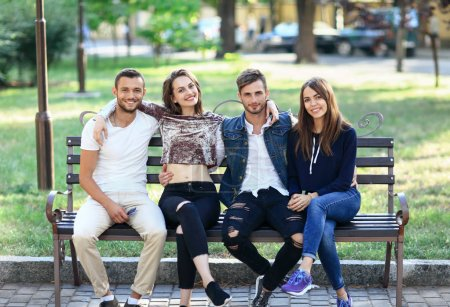 young friends sitting on bench