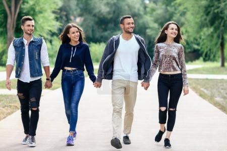 Photo pour Jeunes amis dans des vêtements casual chic main dans la main ensemble en se promenant dans le parc - image libre de droit
