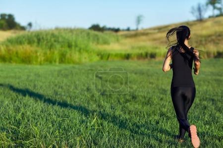 woman running on green meadow