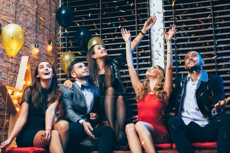 Photo for Group of friends enjoying party and throwing golden confetti, while sitting on couch in club - Royalty Free Image