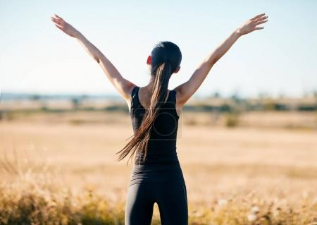 back view of sports woman with rising hands in field