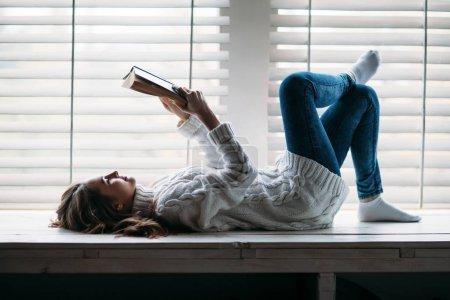 Photo pour Femme lecture livre couché sur rebord de fenêtre à la maison - image libre de droit