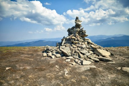 Stone cairn on mountain against blue sky with clouds. Mound on elevation, in desert area. Commemorative dolmen for travelers in picturesque place. Picturesque nature scen