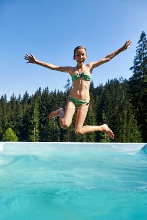 Teenager girl falls into swimming pool outdoor and shouts. Schoolgirl enjoys vacation in nature. Sanatorium surrounded by pristine forest nature. Active leisure in open air and scenic landscape