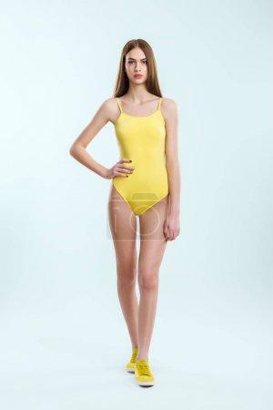 Photo pour Portrait pleine longueur de jeune belle fille en maillot de bain jaune et baskets. Plage, repos, sport, concept relax - image libre de droit