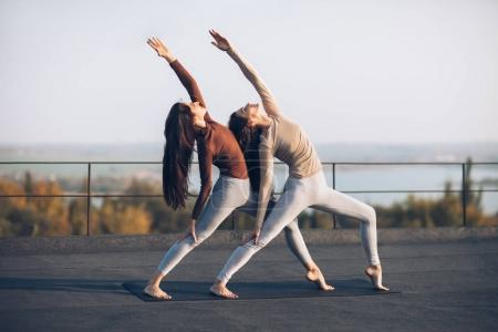Girls synchronously perform double pose warrior