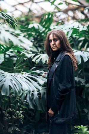 Stylish beautiful woman posing on nature background in bush. Fashion concept