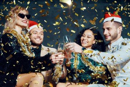 Photo pour Ami (e) s heureux (e) s multiethniques portant un toast au champagne pour célébrer Noël ou Nouvel An, se féliciter et faire la fête - image libre de droit