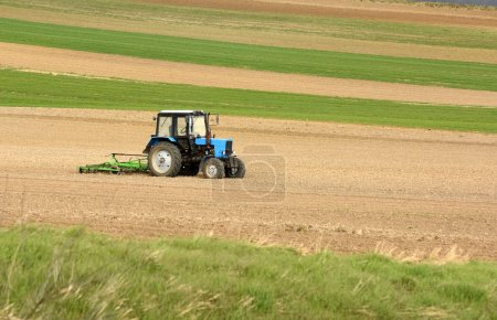 Photo for Tractor at work cultivating a field in spring, farmland, plowed field, - Royalty Free Image