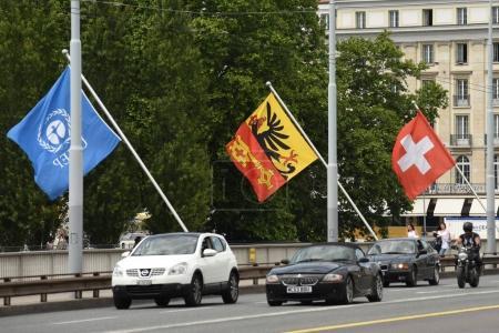 Foto de Ginebra, Suiza - 05 de junio de 2017: Coches y bandera suiza de Ginebra en el puente de Ginebra, Suiza . - Imagen libre de derechos