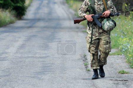 Photo pour Un soldat armé patrouille sur la route. Forces armées, troupes, armée. Est de l'Ukraine . - image libre de droit