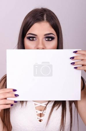 girl holding a paper over her mouth.