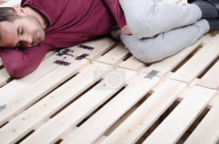 man lying on  wooden bed