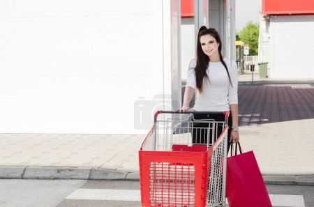 woman shopping with trolley and bags