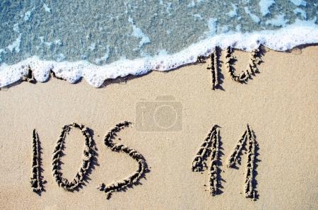 Photo pour Nouveau système d'exploitation IOS 11. Texte sur la plage de sable . - image libre de droit