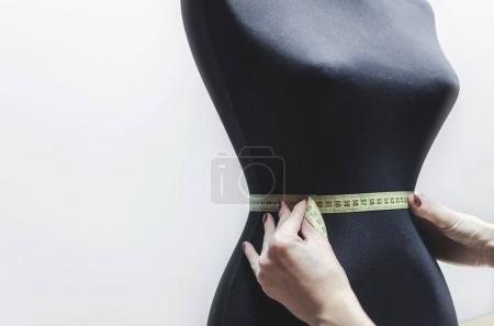 female arms take measure on Black sewing mannequin on white wall background