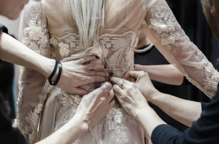 Beautiful bride dress decorated with beads and lace, detail of hands adjusting wedding dress lace