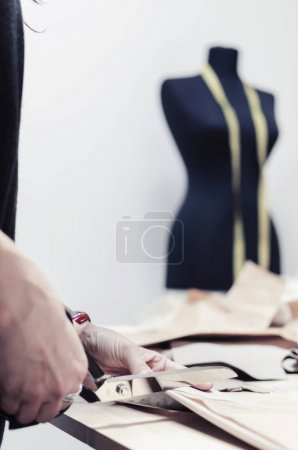 close-up of professional female tailor using scissors and draft design cardboard on cloth material