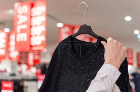 Photo for Woman hand finding women's fashion clothing hangs on cock in a clothes store. Fashion and Accessory Concept - Royalty Free Image