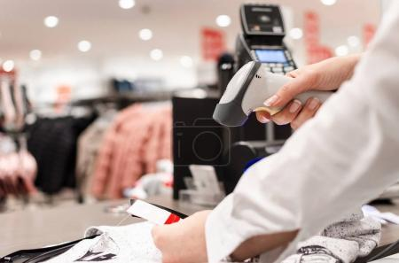 Cropped shot of female hand, Woman or worker holding bar code scanner and scanning card or paper on clothes