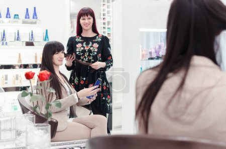 close-up of hairdresser speaking with glamour female in beauty salon
