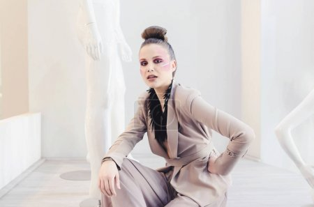 Fashionable woman posing in business jacket and wide-leg pants