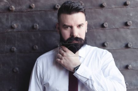 Handsome young bearded man in classic shirt holding beard and looking at camera