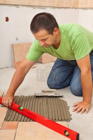 Man laying ceramic floor tiles - checking lines with a level