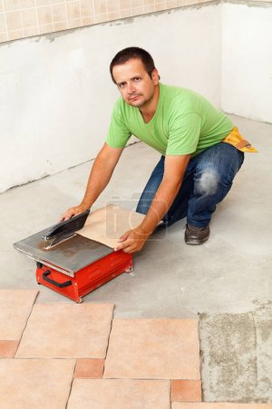 Man cutting ceramic floor tiles with electric cutter