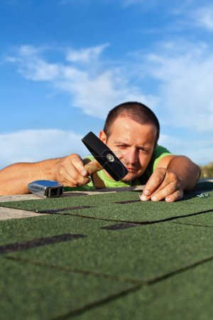 Man fastening bitumen roof shingles with nails and hammer