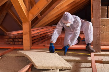 Man laying rockwool panels in the attic of a house