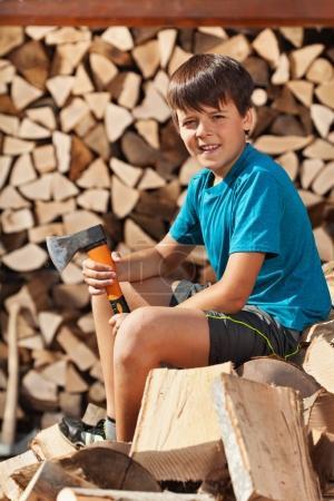 Teenage boy sitting on heap of firewood