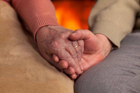 Photo for Senior old hands holding in front of fireplace - closeup, commitment and resilience concept - Royalty Free Image