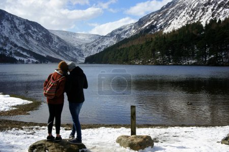 Two people on the shore of the mountain lake.Upper Lake.Glendalough.Wicklow Mountains.Ireland.