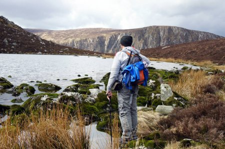Tourist on the shore of the small glacial lake Arts in the Wicklow Mountains.Ireland.