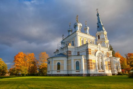 Sunset landscape of beautiful Orthodox church on the meadow, fall time. Stameriena, Latvia.