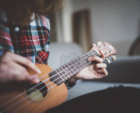 young girl learning to play ukulele