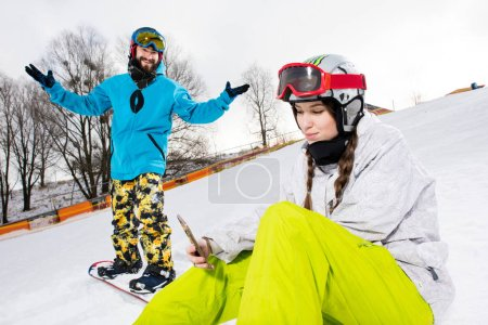 Female snowboarder using smartphone