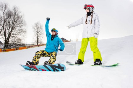Photo for Young couple of snowboarders having fun on snow-covered hill - Royalty Free Image