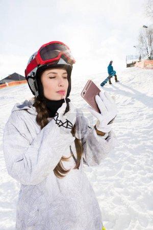 Female snowboarder applying lip gloss