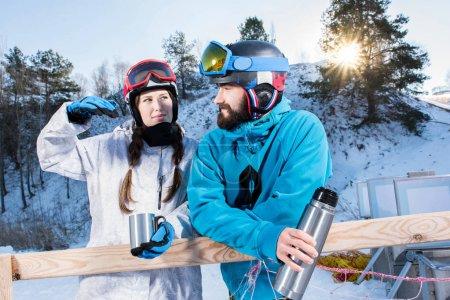 Photo pour Heureux jeune couple de surfeurs des neiges boire du thé et parler au coucher du soleil - image libre de droit