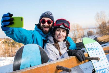Photo pour Jeune homme et une femme embrassant et en prenant selfie avec planches à neige - image libre de droit