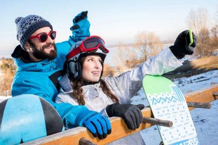 Photo pour Jeune homme et femme embrassant et prenant selfie avec snowboards - image libre de droit
